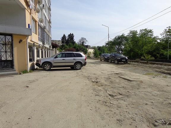 Прямо дорога, занятая машинами, справа времянка с ямами и торчащими люками